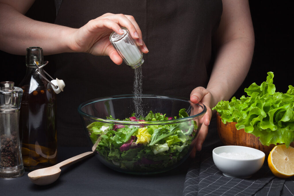 Woman chef in the kitchen preparing vegetable salad. Healthy Eating. Diet Concept. A Healthy Way Of Life. To Cook At Home. For Cooking. The girl sprinkles salt in a salad on a dark background;