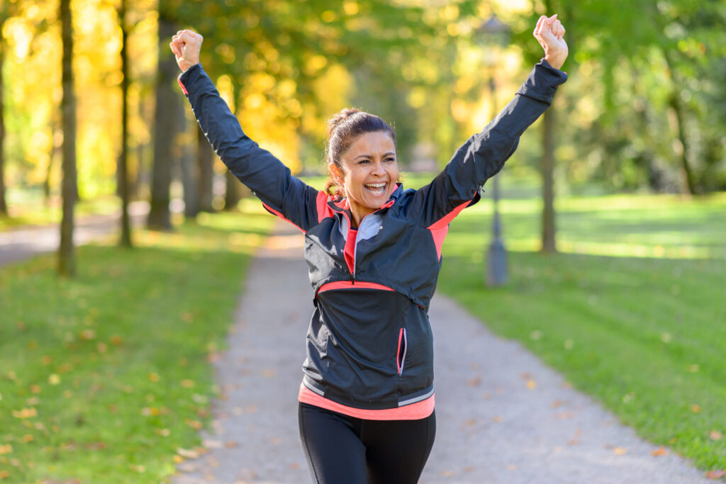 Happy fit middle aged woman cheering and celebrating as she walks along a rural lane through a leafy green park after working out jogging