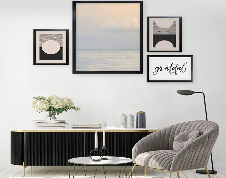A gallery wall in a living room. Creams and black.
