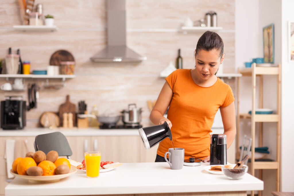 Woman pouring hot coffee in cup in the morning from pot. Housewife at home making fresh ground coffee in kitchen for breakfast, drinking, grinding coffee espresso before going to work;
