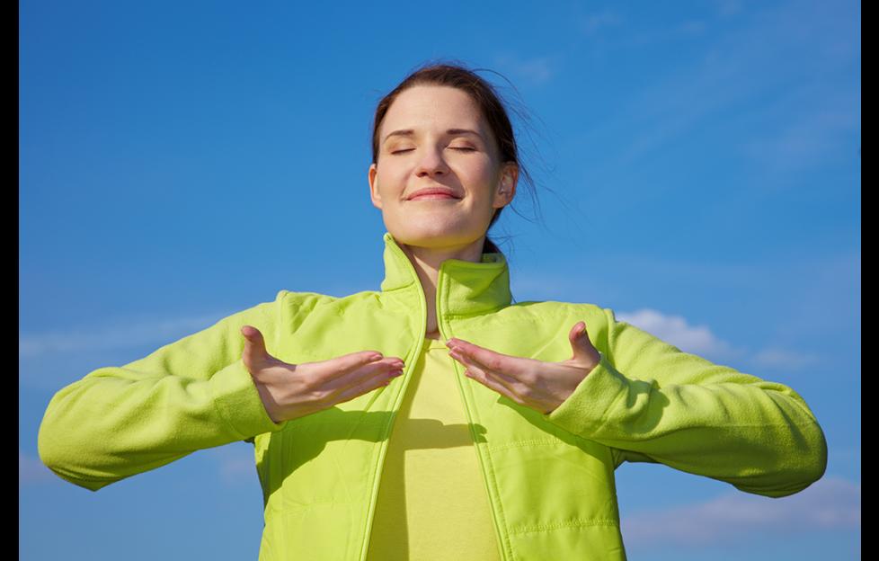 Brunette in lime green jacket doing breathing exercises outdoors