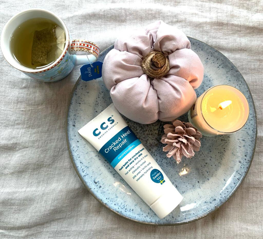 Mug of herbal tea with candle and CCS Foot cream