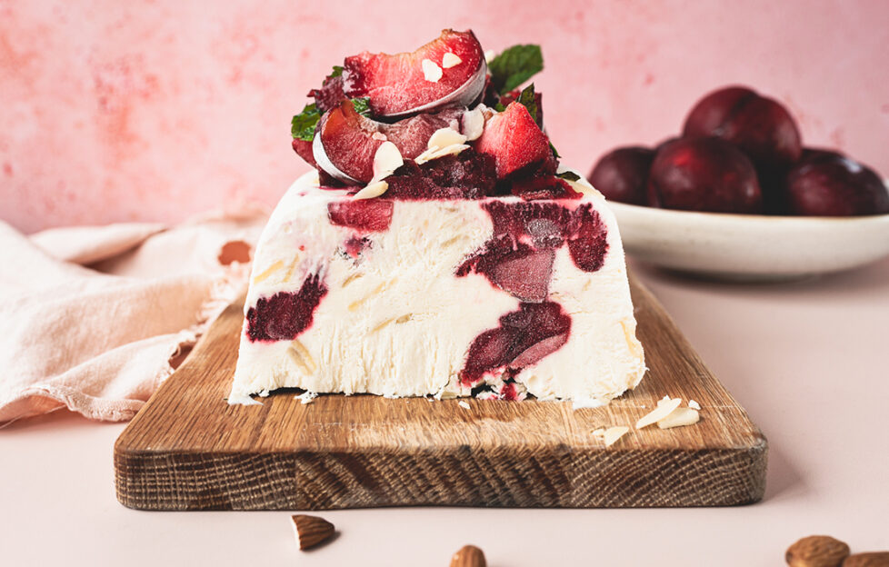Slice of plum semifreddo on chopping board, ice cream loaf with red plums mixed in and piled on top