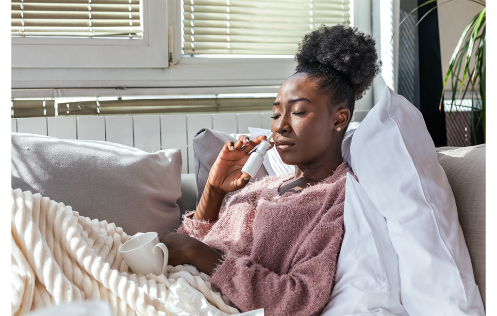 Black lady in bed ill with cup of tea and using nasal spray