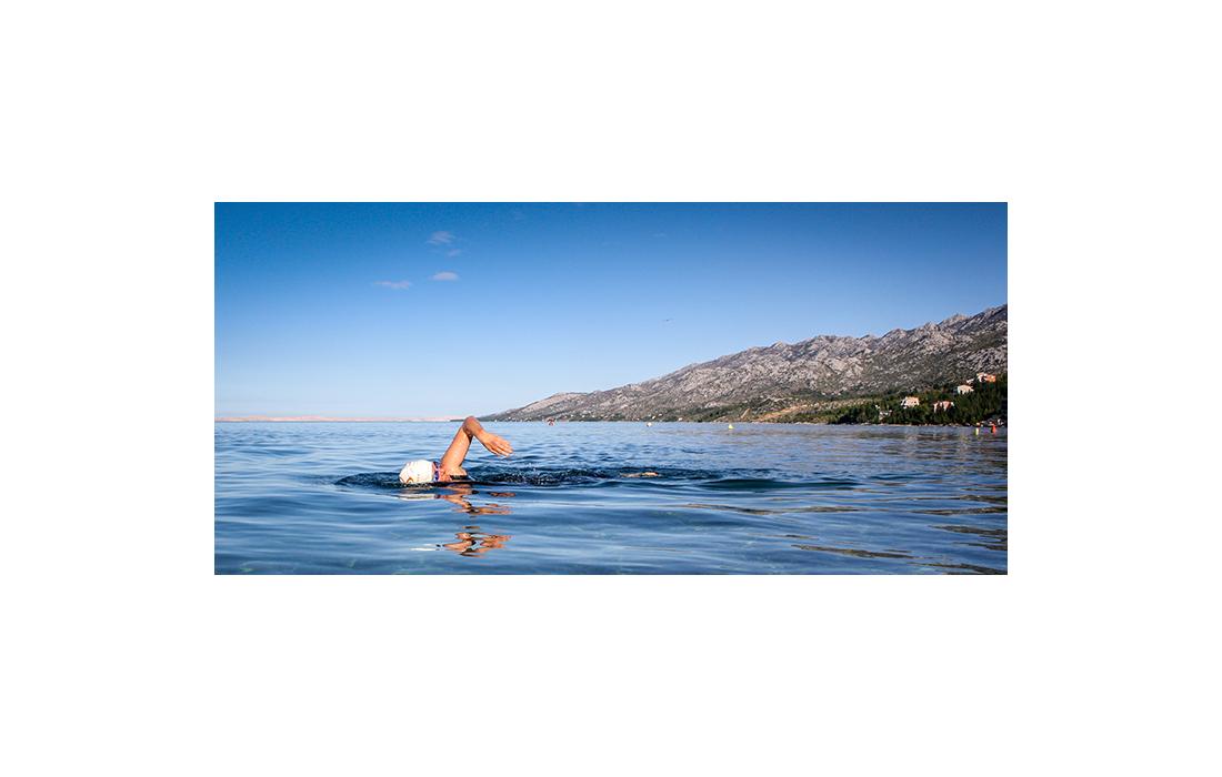 Woman in swimming cap swimming across loch
