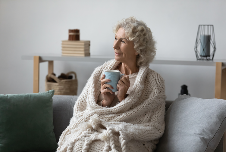 Older woman with blanket around her and cup of coffee sitting on settee