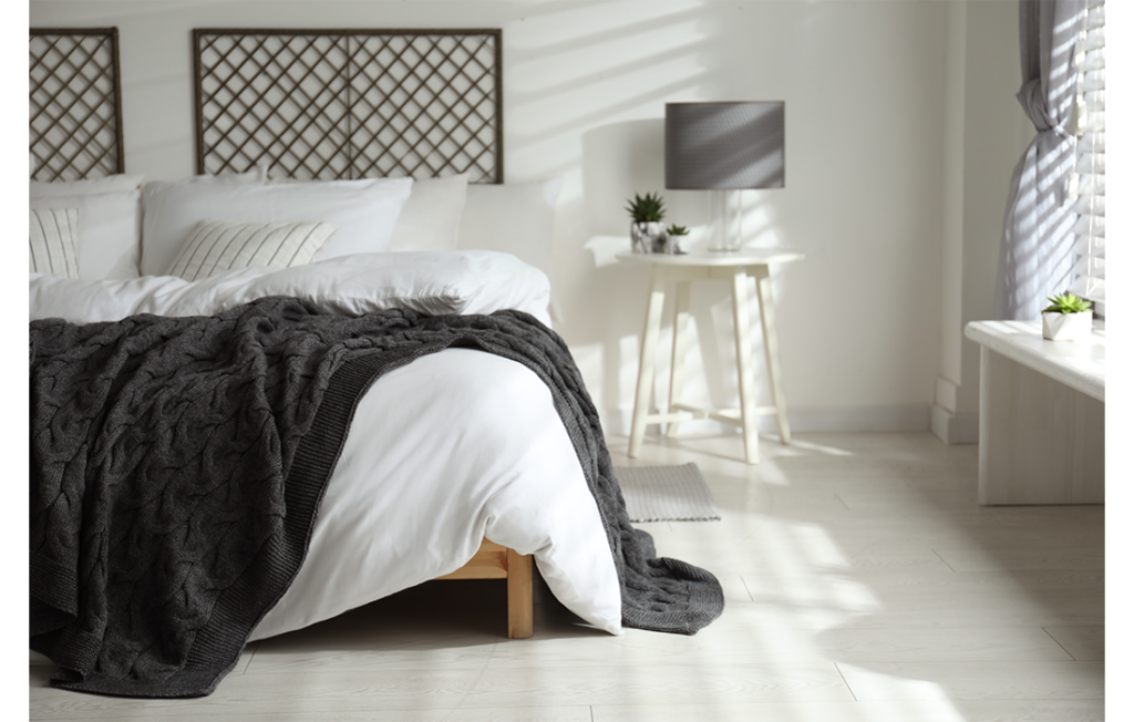 Bed with white linens and grey blanket