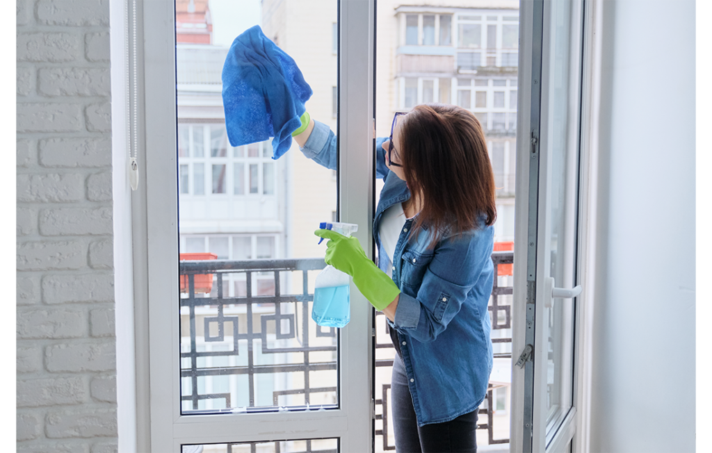 Woman cleaning outside of patio doors on a balcony