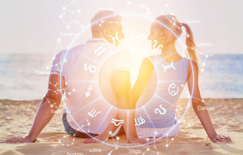 Couple on beach at sunset, star signs overlay