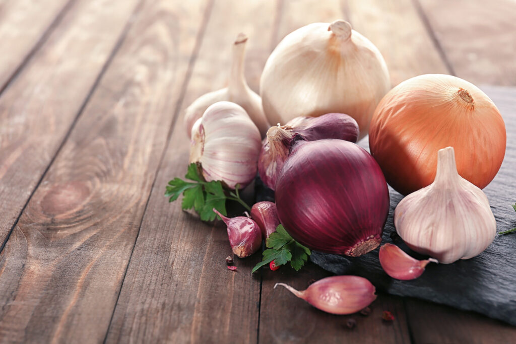 Slate plate with fresh garlic and onion on wooden table, closeup;