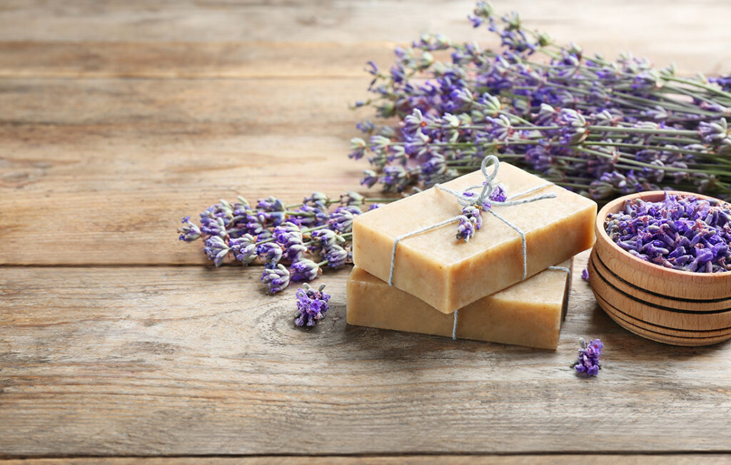 Handmade soap bars with lavender flowers on brown wooden table.
