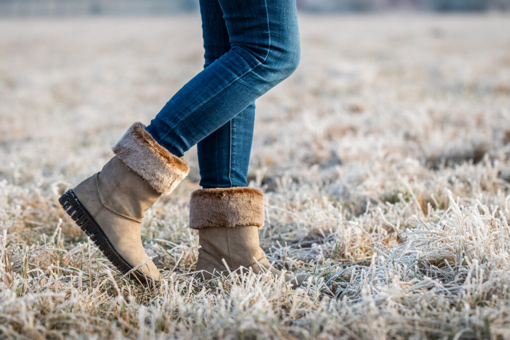 Woman wearing leather boots with fur at winter. Walking outdoors in hoarfrost. Female legs with skinny jeans. ;