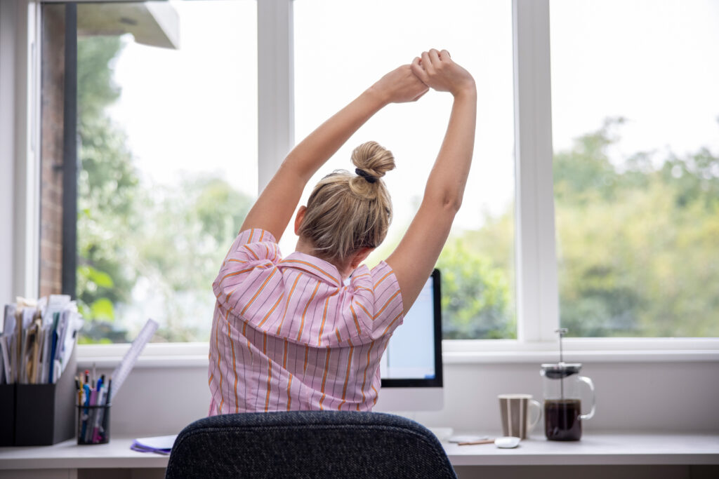 Rear View Of Woman Working From Home On Computer  In Home Office Stretching At Desk;