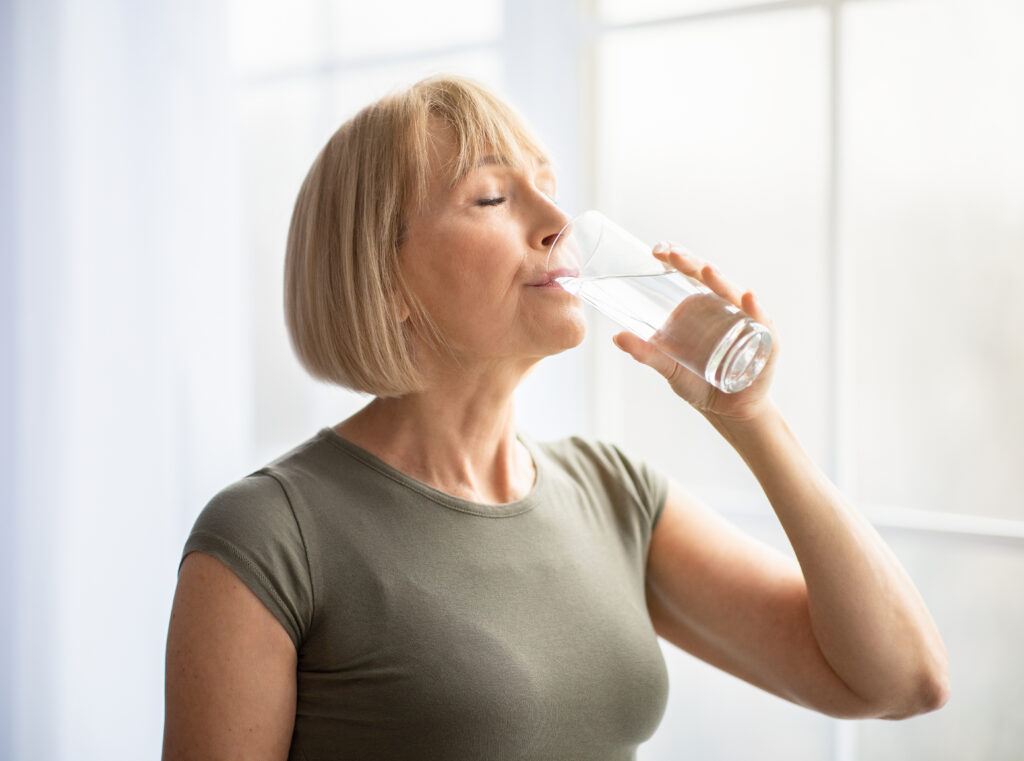 Fit senior woman drinking clear water during her workout break at home. Mature Caucasian lady staying hydrated after sports training. Healthy lifestyle and wellness concept