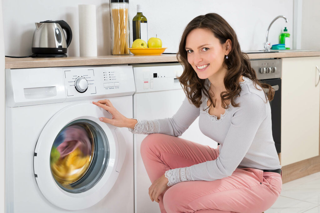 Young Happy Woman Cleaning Multi-colored Clothes In Washing Machine At Home;