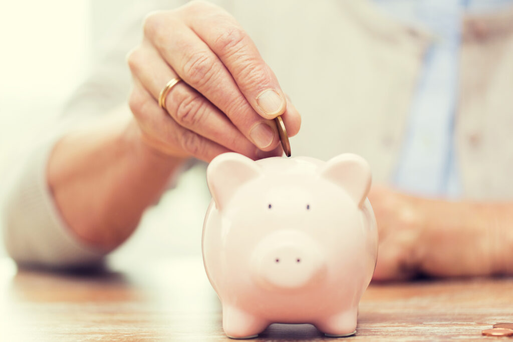 savings, money, annuity insurance, retirement and people concept - close up of senior woman hand putting coin into piggy bank;