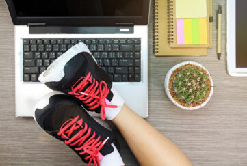 Business women laying her legs in sport shoes over the laptop, Life and work balance concept. (Lighting effect);
