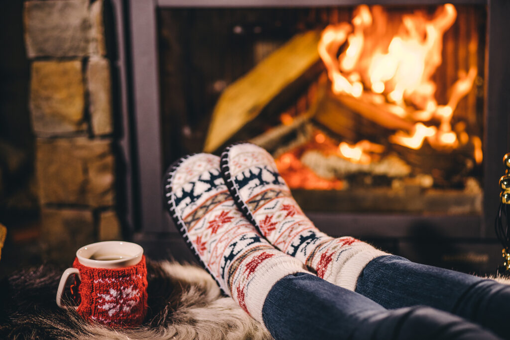 Feet in woollen socks by the Christmas fireplace. Woman relaxes by warm fire with a cup of hot drink and warming up her feet in woollen socks. Close up. Winter and Christmas holidays concept. ;