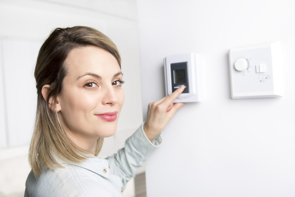 A woman set the thermostat at house.;