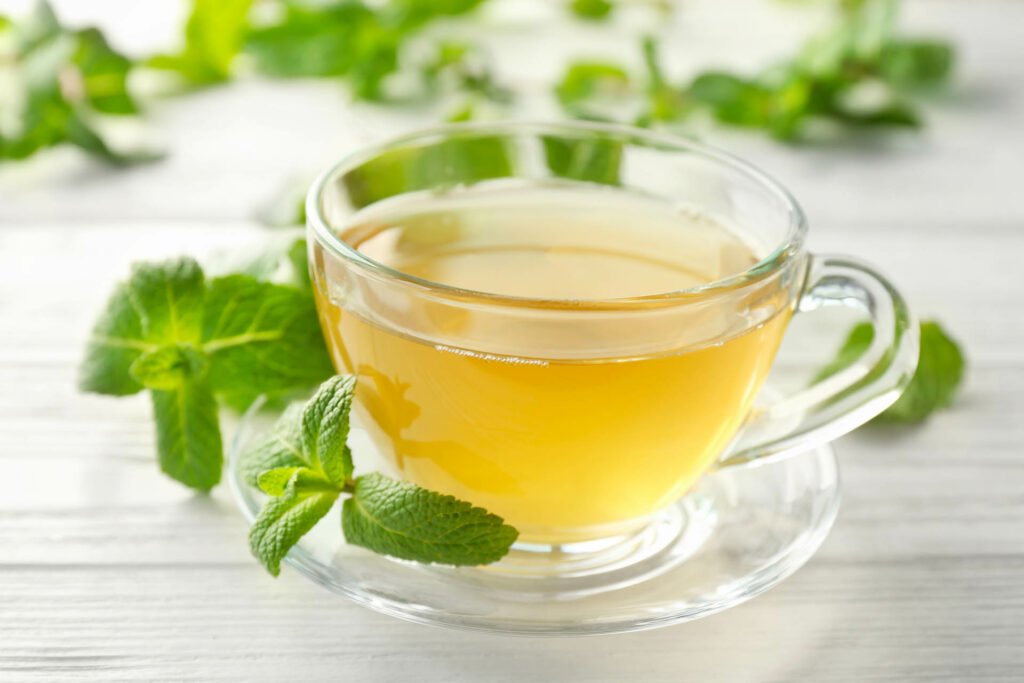 Cup of hot aromatic tea with lemon balm on wooden table;