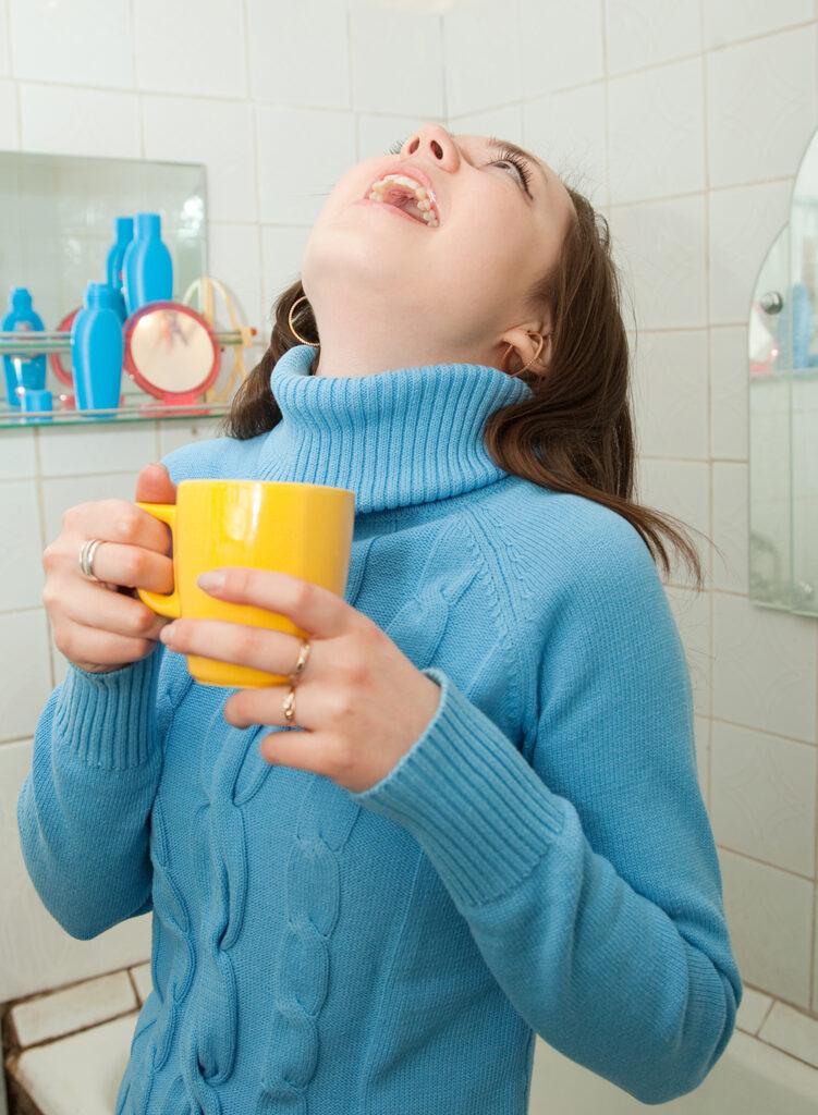 Brunette gargles with yellow mug in her bathroom