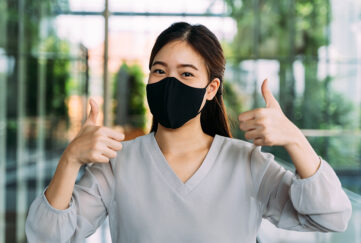 woman in mask gives thumbs up