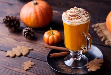 pumpkin spiced latte in glass topped with cream, on stained wooden table with small pumpkins, cinnamon sticks and ginger biscuits