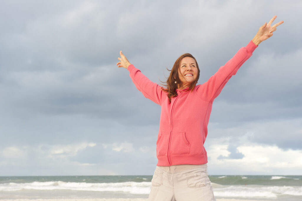 Portrait of positive and happy mature woman at the beach, wearing pink sweater, isolated with ocean and storm clouds as background and copy space.;