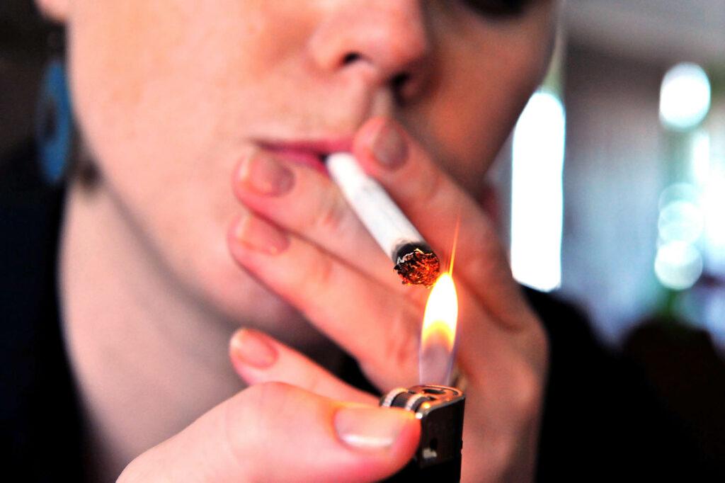 Concept photo of a woman smoking a cigarette.;