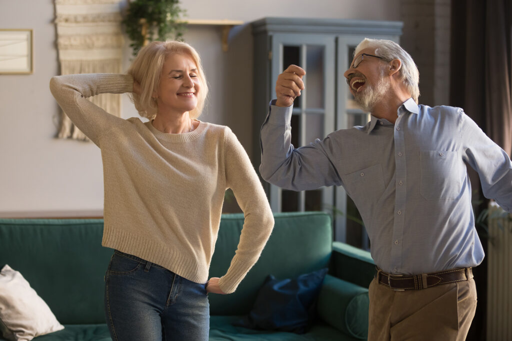 Happy active positive retired elder couple dancing together in living room, cheerful old senior husband and mature middle aged fit wife enjoying fun leisure activity laughing bonding moving at home;