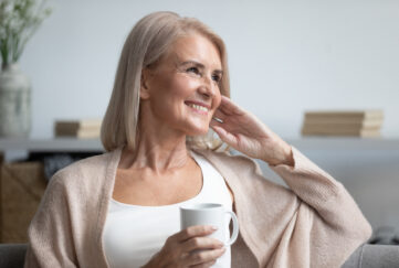 Happy beautiful dreamy old senior middle aged woman sit on sofa relax at home hold cup drink coffee tea looking away thinking dreaming enjoy stress free peaceful mood wellbeing alone in living room;