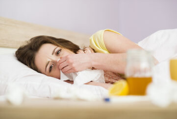 Sick woman lying in bed with high fever. She has cold and flu. In front of her is tea with lemon and honey.;