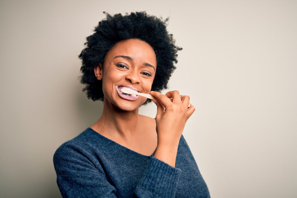 African american woman brushing her teeth using tooth brush and oral paste, cleaning teeth and tongue as healthy health care morning routine;