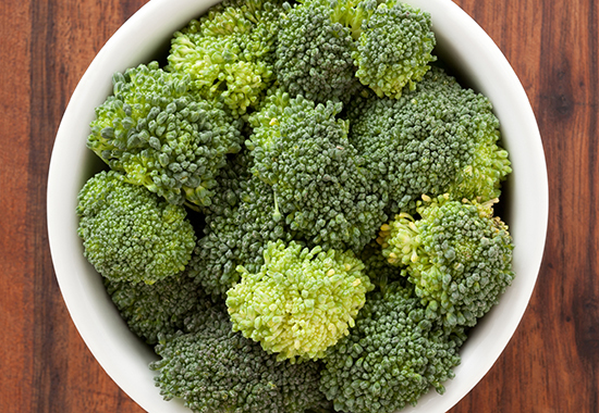 Top view of white bowl full of raw broccoli