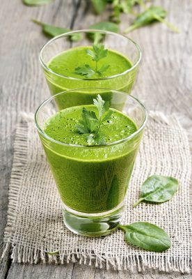 Vegetable spinach smoothie decorated parsley on wooden table