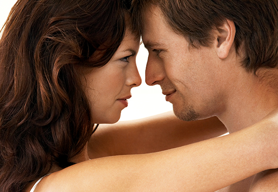 Side view of passionate young couple embracing in bedroom