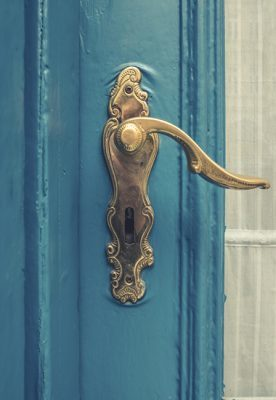 Architectural Detail Of A Vintage Brass Door Handle On A Blue Painted Door