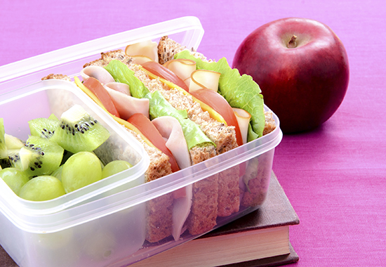 """""""Nutritious filled lunchbox with ham sandwich, kiwi, grapes on book and apple on pink background"""""""