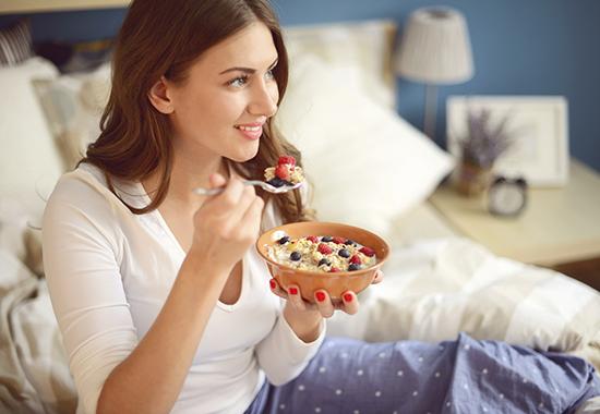 woman in pajamas in bedroom eating muesli with berries