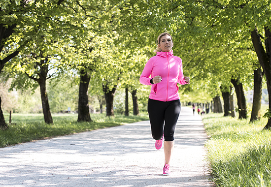Mature woman running through park. She is wearing pink and black sports clothing. Green trees and grass are around her.