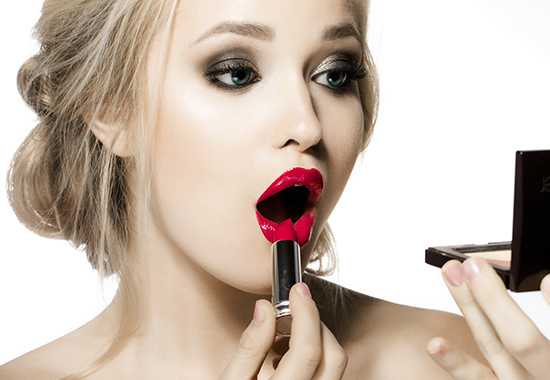 Woman applying lipstick, make-up