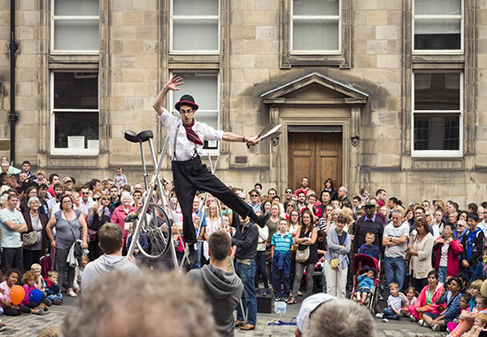 Edinburgh, Scotland, UK - August 3, 2013: A street performer balances on a tightrope, held up by volunteers picked from the crowd on the Royal Mile, on the first weekend of the Edinburgh Festival Fringe.