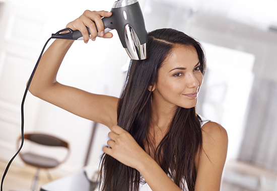 Shot of a beautiful young woman blow drying her hair