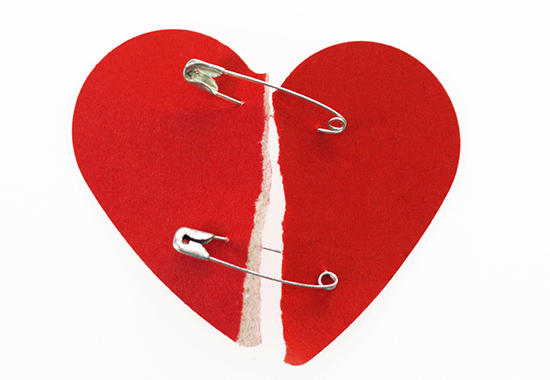 Red broken heart fixed with safety pin