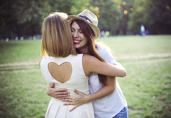 Young female friends embracing together standing in a park.