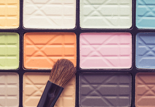Close up eye make up brush on colorful eye shadow palette - beauty makeup cosmetics in vintage tone filter