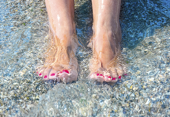 Feet washed in surf on tropical sandy beach