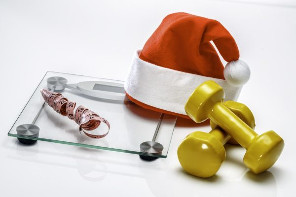 Fitness on Christmas: Santa hat with scale, measuring tape and dumbbells. The festive season is upon us; that can only mean diet debauchery, abandoned fitness regimes and six-hour TV marathons. But it doesn't have to be this way at all. With a little planning and tiny self-discipline, it is perfectly possible to enjoy a happy Christmas and enter the New Year feeling fit without getting fat. A regular exercise regime is essential for a healthy and happy lifestyle. Physical activity helps maintain a healthy weight range. It improves body strength, fitness and has positive psychological effects. People who exercise regularly generally live happier lives and are less stressed ans sleep better than those who do not.