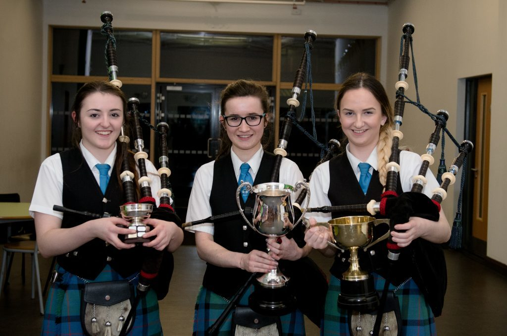 Pipers with their trophies L-R Amber MacDonald, Sine MacRae and Megan Campbell.
