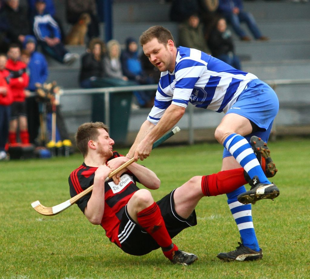 Norman Campbell, Newtonmore, clashes with Oban Camanachd's Gary McKerracher  at Mossfield Stadium last Saturday. Photograph: Kevin McGlynn.